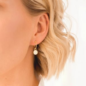yellow gold mini hoop disc earrings on ear